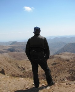 Picture of Bernard with his back to the camera, looking out over the mountain ranges which we are high above.