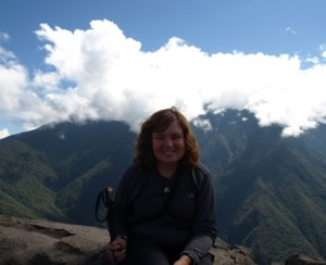 Picture of Cathy sitting at the very summit. The mountains and clouds stretch out behind her.