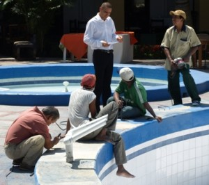 Picture of Franco the manager (standing) as he stresses about the pool. The waiter on his right holds the new circular sander.