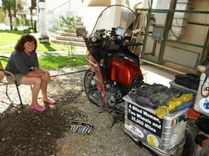 Picture of Cathy. She is smiling sat by Bertha as the starter motor has worked!
