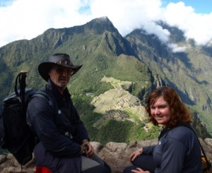Picture of Bernard and Cathy sitting dangling their legs. Machu Picchi is way off below them in the background.