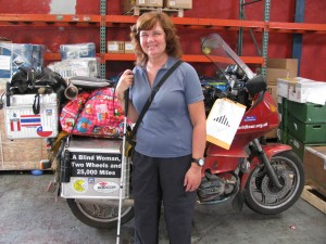 Picture of Cathy standing in front of Bertha at the air freight warehouse with all of our equipment strapped onto the seat.