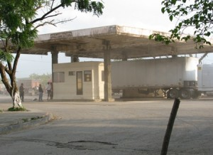 Picture of part of the Nicaraguan border post. A white haze fills the air from the dust kicked up by vehicles.