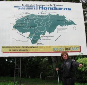 Picture of CAthy standing underneath a large bill-board showing a map of Honduras. She is pointing towards the direction we are about to set off.