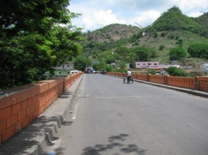 Picture of the long bridge which separates the two countries. The road is empty apart from a small cycle rickshaw.