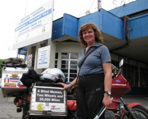 Picture of Cathy underneath the El Salvador gateway to the country.