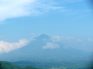Picture of one of the many volcanoes which inhabit this part of the world. It is in the distance and the whole scene is blue due to the brightness of the sun.