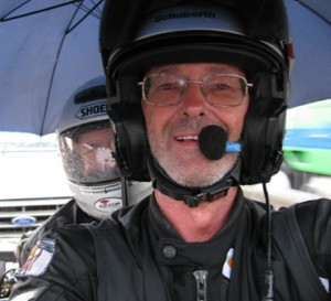 Picture of Bernard and CAthy sitting on the bike sheltering under the umbrella at the USA border before crossing.
