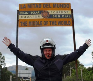 Picture of Cathy with her arms out in a victory wave underneath the sign indicating we have reached the centre of the world.