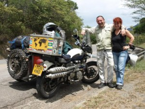 Picture of Andy and Maya stood beside their Triumph. Andy has his arm around Maya and they are both smiling.