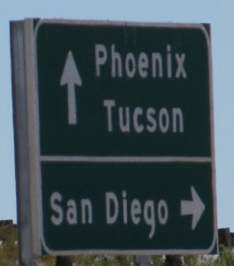 "Picture of a road sign saying ""Phoenix / Tucson straight ahead, San Diego turn right."""