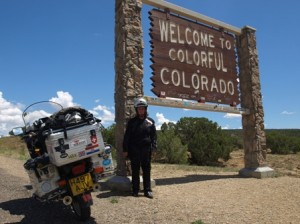 "Picture of Bertha and Cathy standing beside a sign which declares ""Welcome to Colourful Colorado."""