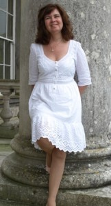 Picture of Cathy leaning against a large stone pillar. She is wearing a white dress.