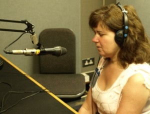 Picture of Cathy sat in the studio wearing headphones and talking into a microphone